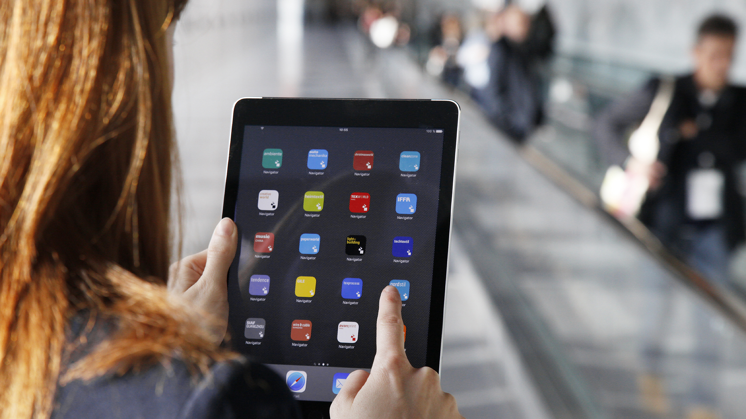 Woman clicks on a Messe Frankfurt app on a tablet.